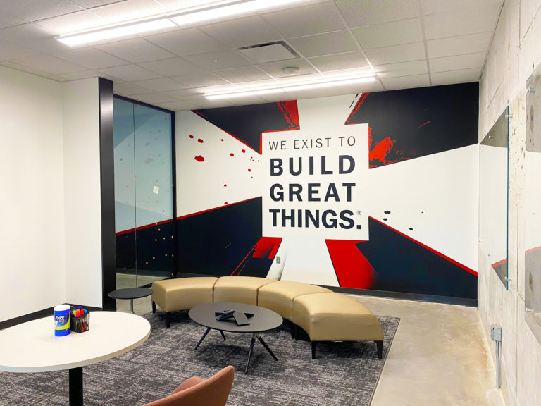 """Modern office interior with """"We Exist to Build Great Things"""" printed on the wall."""