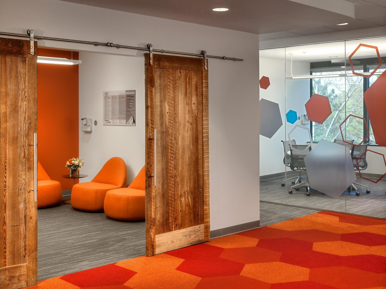 Office interior with wood barn doors and bright orange furniture and carpets.
