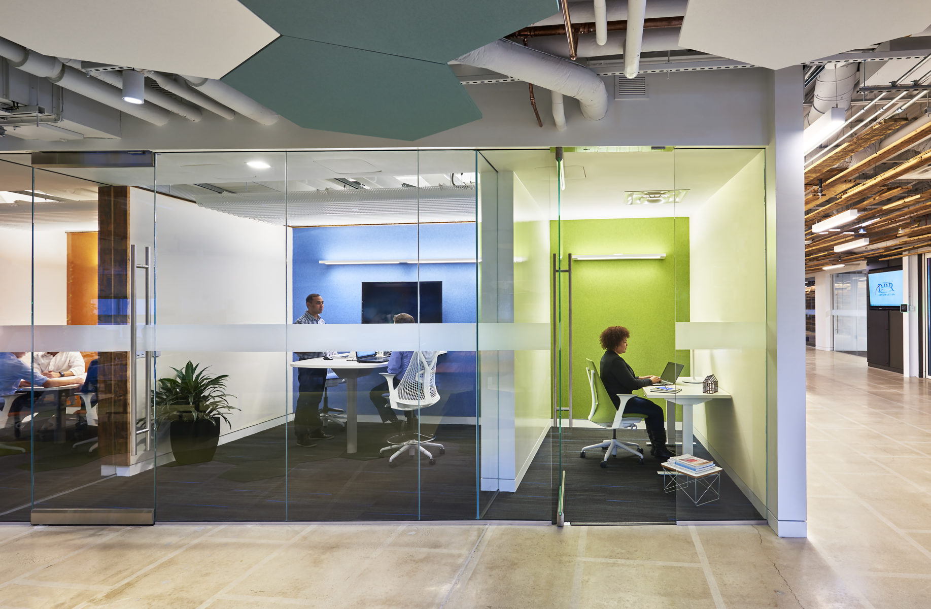 Meeting rooms with brightly colored accent walls and glass fronts.