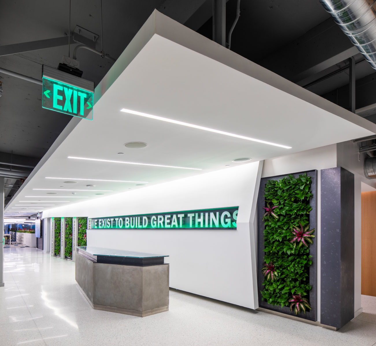 """Office interior with """"We Exist to Build Great Things"""" on the wall in between living walls of plants."""