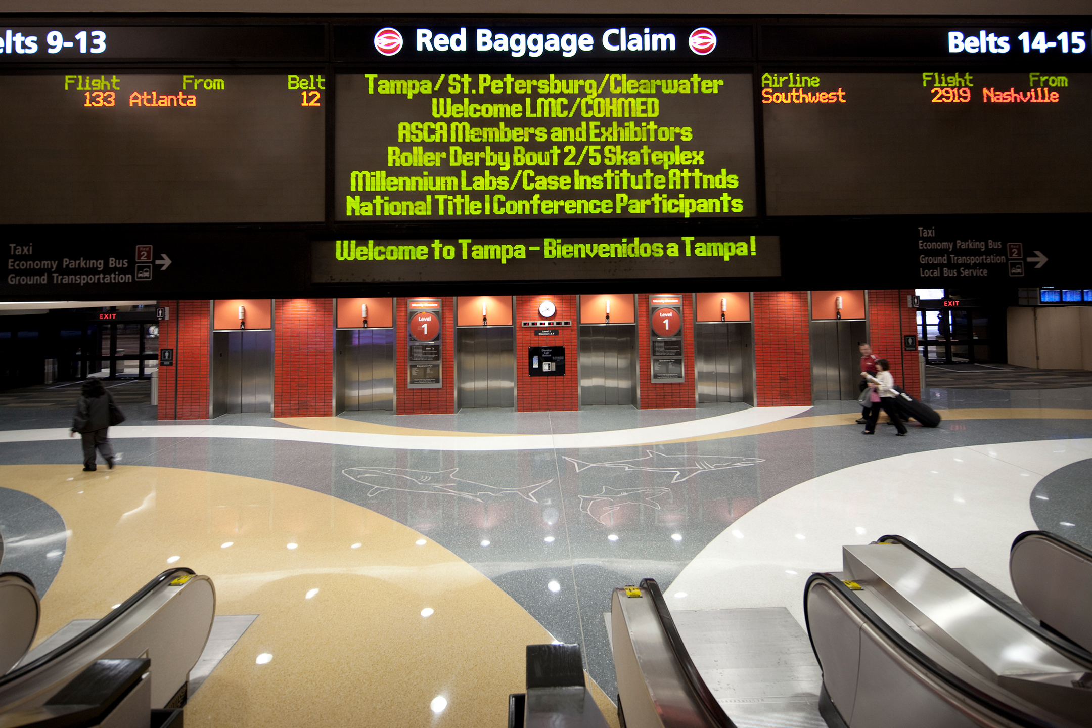 Baggage claim area at the bottom of a set of escalators