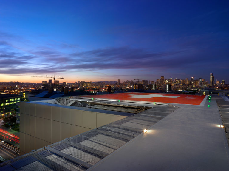 Rooftop helipad at night with a city skyline stretching behind it.