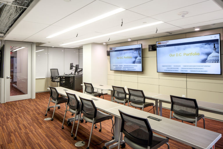Interior of meeting room with desks.