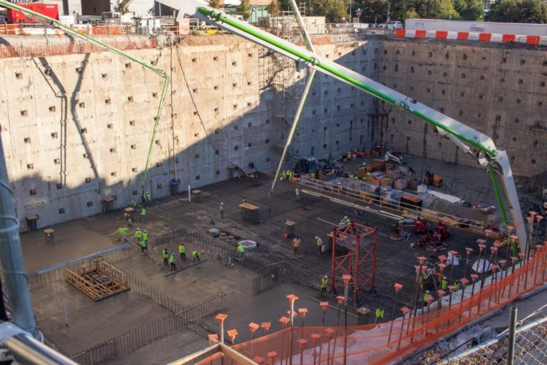 Teams work to pour and lay the concrete MAT in the foundation of the building.