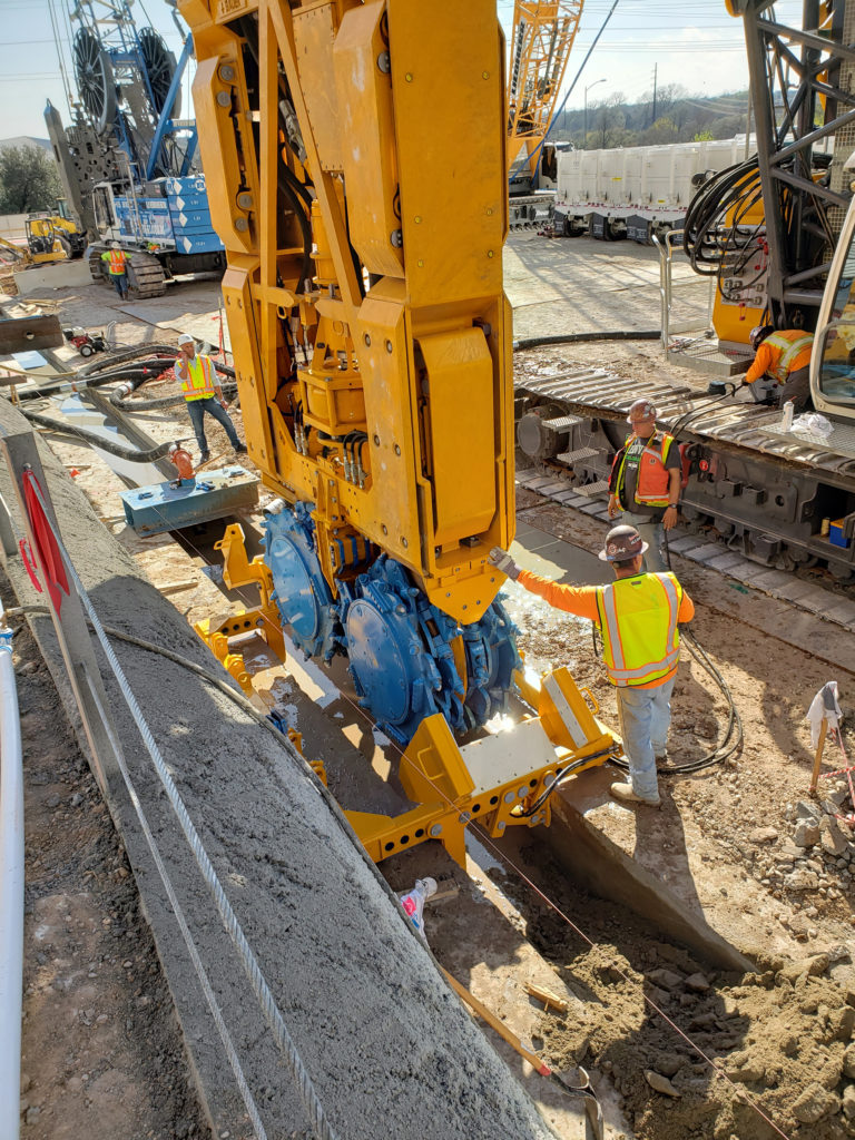 workers control construction equipment