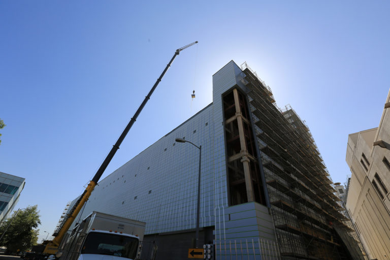 A crane lifts materials to the roof of the building for construction.