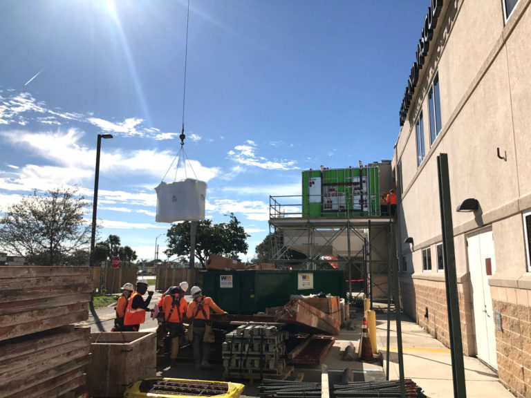 Construction jobsite with men lifting an item from a crane.