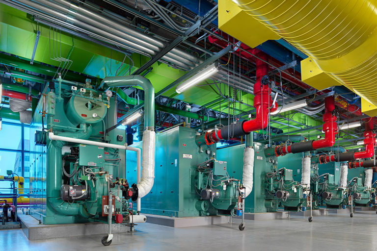 Pipes and machinery are shown in a row with system tubes intertwining.