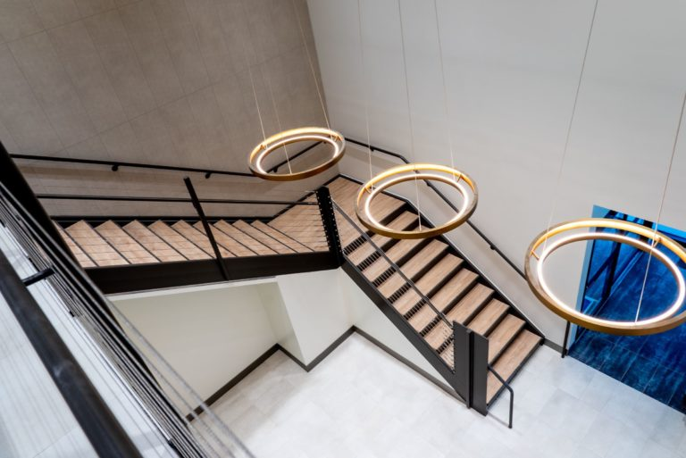 Interior shot of building hallway with stairs.