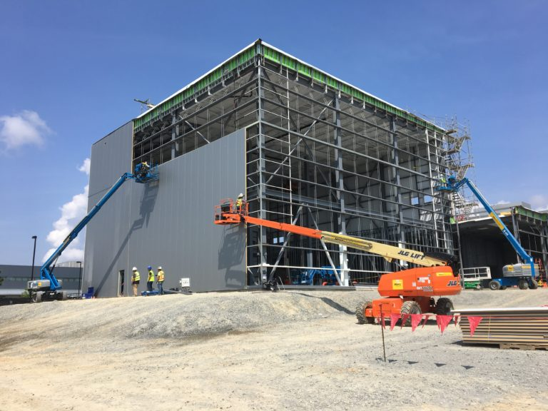 Cranes lift portions of the exterior walls for installation