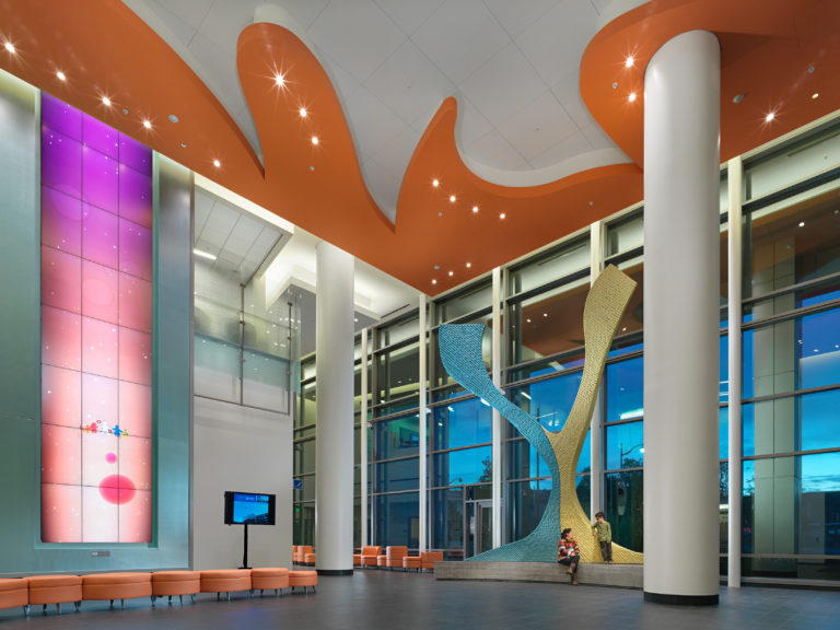 An architecturally decorated lobby with orange ceiling detail and sculpture.