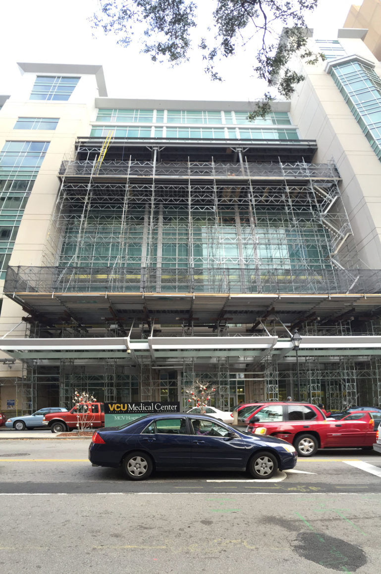 Traffic drives by the VCU hospital covered in scaffolding