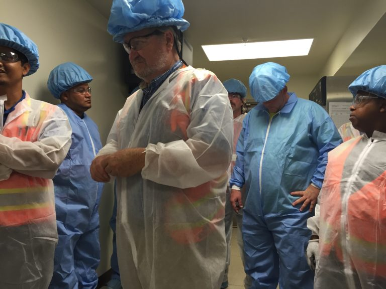 Workers and staff wear protective gear and safety suits on site.
